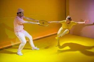 Zdjęcie ze spektaklu Ra-dość. Dwójka aktorów stoi na żółtej podłodze. Jedna ściana jest bladoróżowa, druga żółta. Aktor ubrany jest w bladoróżowe ubrania, a aktorka w żółte. Stoją na przeciwko siebie i próbują sobie wyrwać żółte koło od roweru.