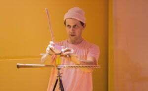 Ubrany w bladoróżową koszulkę i czapkę aktor próbuje ustawić piramidę z rekwizytów - rakietki do badmintona, żółtego odważnika, różowej chochli.