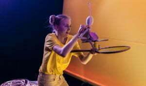 Zdjęcie ze spektaklu Ra-dość. Aktorka ubrana w żółtą koszulkę próbuje utrzymać w dłoniach piramidę z rekwizytów - rakietki do badmintona, żółtego odwaznika, różowej chochli i lalki.