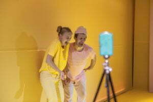 Zdjęcie ze spektaklu Ra-dość. Dwoje aktorów - on ubrany w bladoróżowy strój, ona w żółty - pozuje do zdjęcia robiąc krzywe miny po zjedzeniu cytryny.
