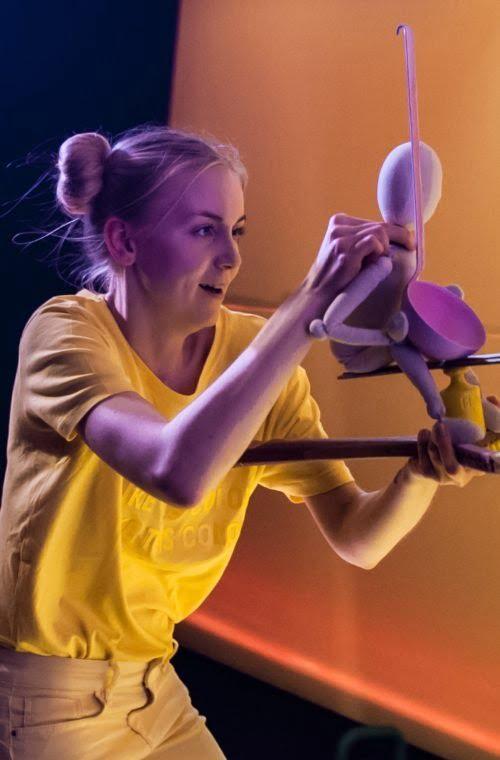 Zdjęcie ze spektaklu Ra-dość! Aktorka ubrana w żółtą podkoszulkę trzyma w dłoniach drewnianą lalkę i różową chochlę.