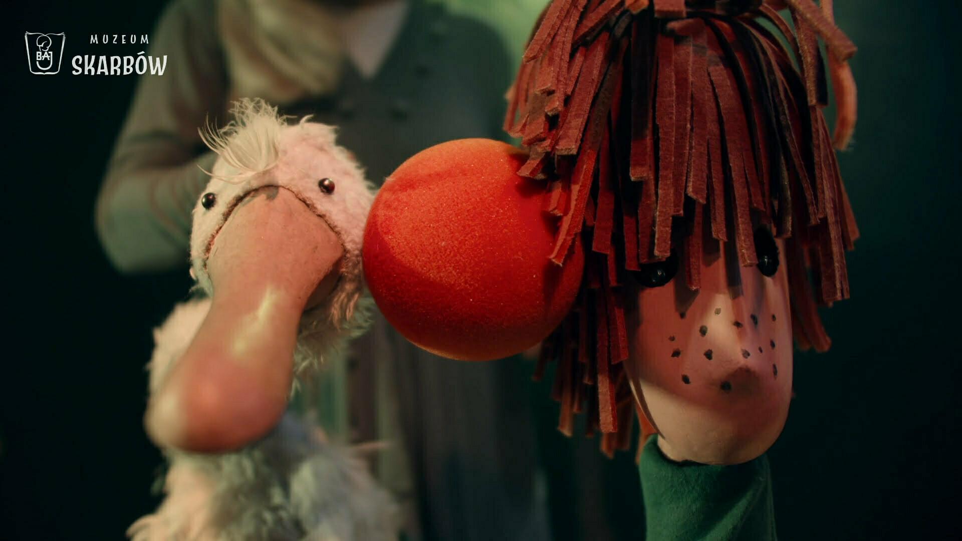 Zdjęcie ze spektaklu Muzeum Skarbów. Na zdjęciu po lewej stronie Gęś, po prawej główny bohater Andrzejek. Bohaterowie widoczni są od szyi w górę. Razem przyciskają uszy do pomarańczy, która znajduje się pomiędzy ich głowami.