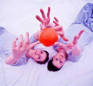 Zdjęcie ze spektaklu Śpij. Na białym materiale leżą dwie aktorki ubrane w jasne bluzki. Wyciągają ręce do góry i trzymają w nich pomarańczę.