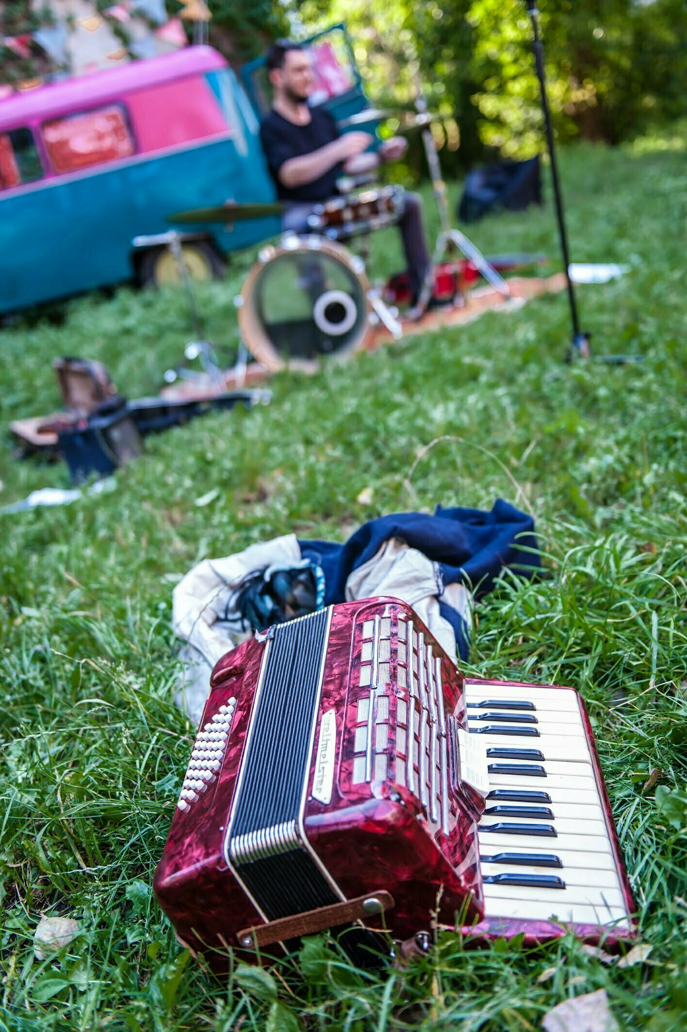 Zdjęcie z koncertu zespołu Bardzo Duży Dom. Instrumenty rozstawione są na zielonej trawie. Z przodu widać leżący akordeon, w tle perkusitę siedzącego przy perkusji.