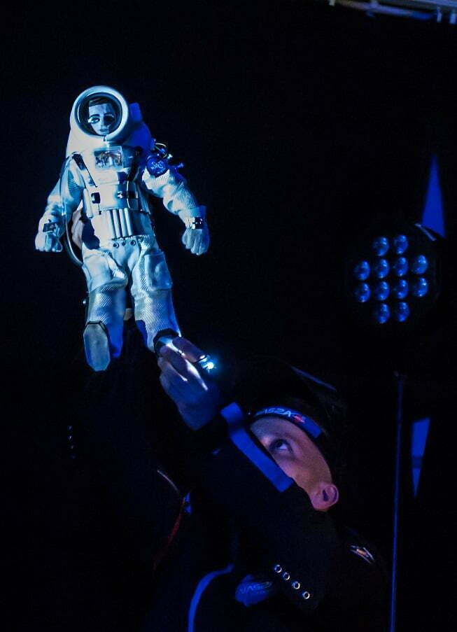 Zdjęcie ze spektaklu Ile waży jabłko na Marsie? Astronauta w ciemnym stroju patrzy w górę na trzymaną w ręku lalkę austronauty w białym, grubym kombinezonie.
