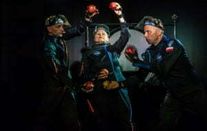 Zdjecie ze spektaklu Ile waży jabłko na Marsie? Trzech astronautów w czarnych kombinezonach trzyma w rękach jabłka. Trzymają je na różnej wysokości jakby próbowali je zważyć.
