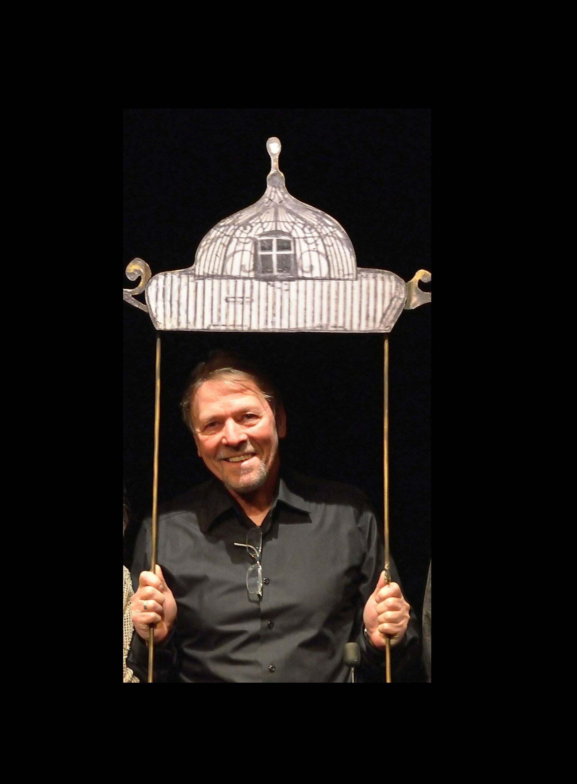 Zdjęcie Janusza Ryla-Krystianowskiego. Uśmiechnięty mężczyzna stoi na czarnym tle i trzyma nad sobą dach - element scenografii.