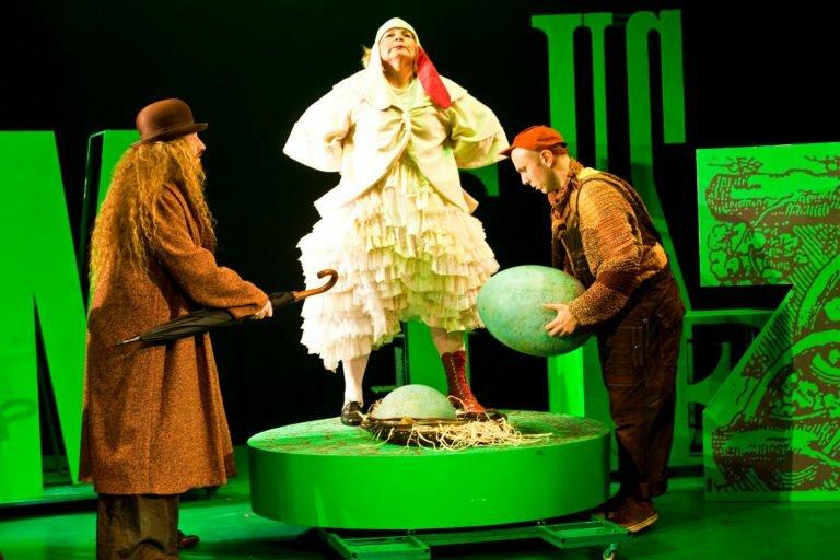 Zdjęcie ze spektaklu Tymoteusz wśród ptaków. Przebrana za kurę aktorka stoi z głową uniesioną do góry na gnieździe, w którym leży jajko. Obok nachylony nad gniazdem chłopiec trzyma w rękach drugie, duże jajko.