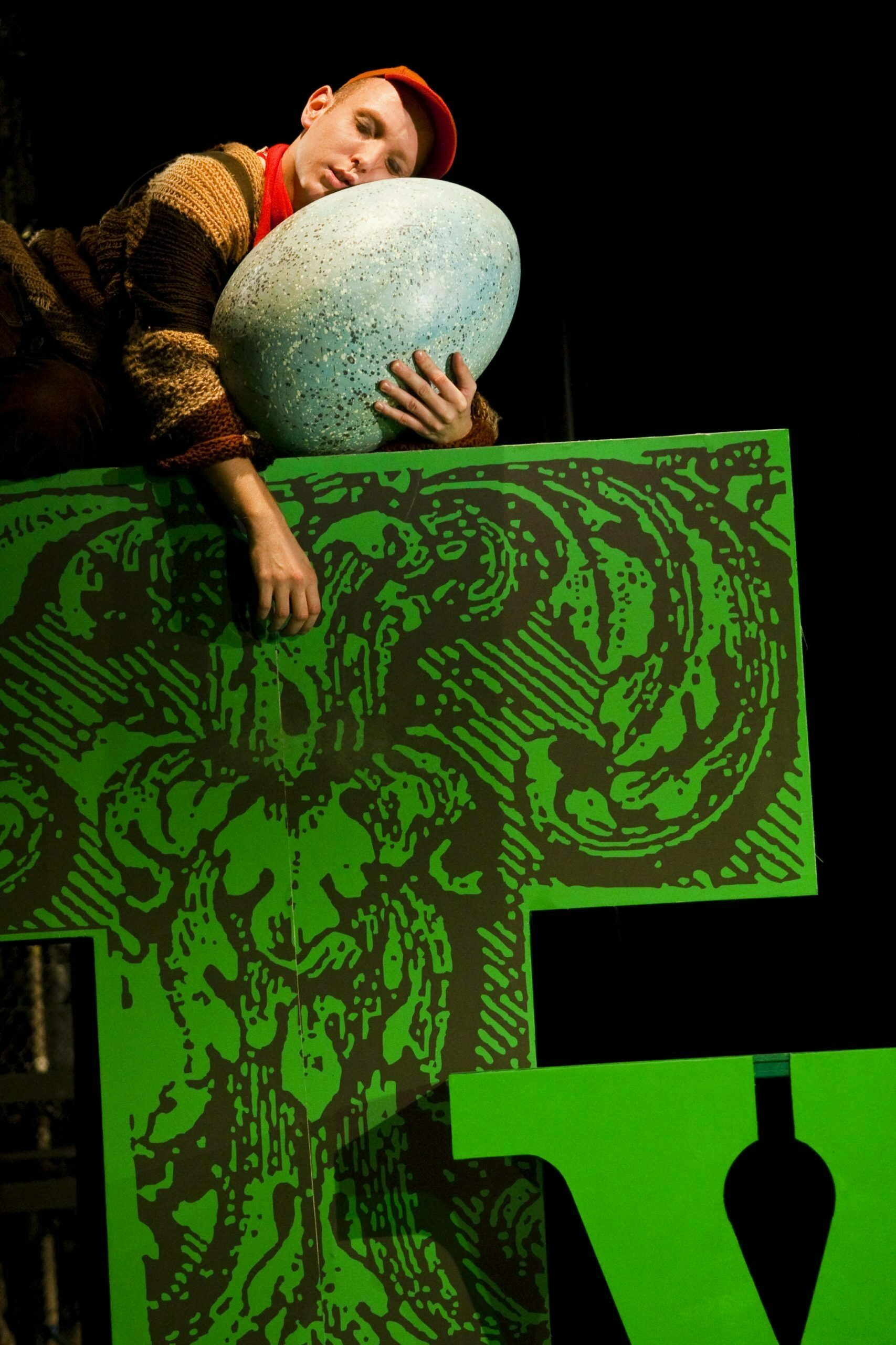 Zdjęcie ze spektaklu Tymoteusz wśród ptaków. Na dużej, zielonej literze T śpi chłopiec w pomarańczowej czapce. Chłopie prztula się do dużego, jasnego jajka.