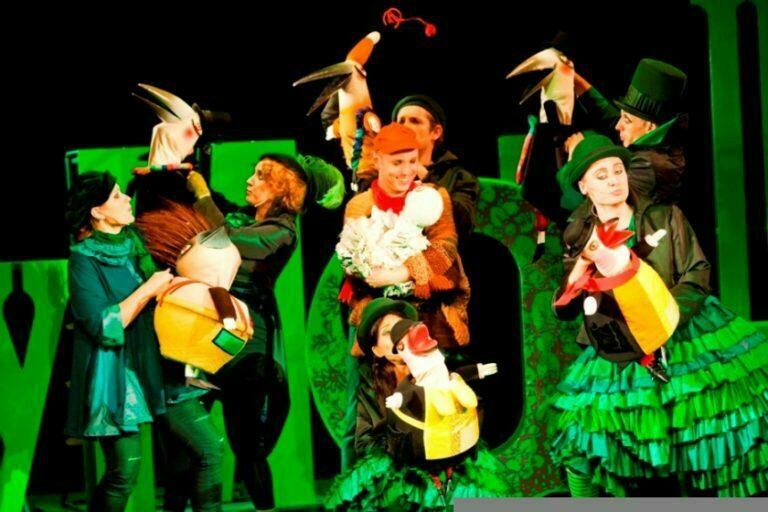 Zdjecie ze spektaklu Tymoteusz wśród ptaków. Sześciu aktorów-lalkarzy trzyma kolorowe lalki ptaków.