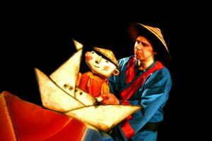 Zdjęcie ze spektaklu Zaczarowane wycinanki. Lalka teatralna siedzi w łódce zbudowanej z figur geometrycznych - trójkątów i trapezów. Animuje nią aktor w granatowym kimonie i trójkątnym kapeluszu.