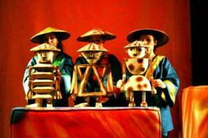 Zdjęcie ze spektaklu Zaczarowane wycinanki. Na pomarańczowym tle stoją trzy aktorki ubrane w granatowe kimona i trójkątne kapelusze. Każda z nich trzyma przed sobą lalkę teatralną. Pierwsza z lewej strony jest zbudowana z trapezów, druga z trójkątów, a trzecia z półokręgów.