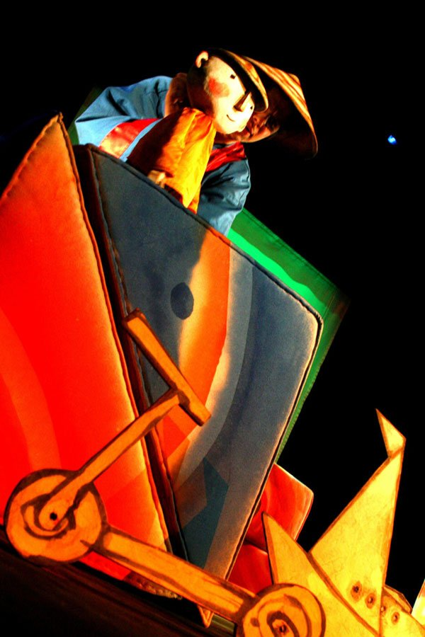 Zdjęcie ze spektaklu Zaczarowane wycinanki. Zza wielokolorowych trójkątów, hulajnogi i łódki zbudowanej z różnych kształtów wyłania się na górze lalka w trójkątnym kapeluszu.