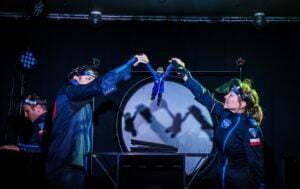 Zdjęcie ze spektaklu Ile waży jabłko na Marsie? Dwóchastronautów w granatowych kombinezonach stoi zwróconych do siebie. Wyciągają przed siebie ręce, w których trzymają małą lalkę astronauty.