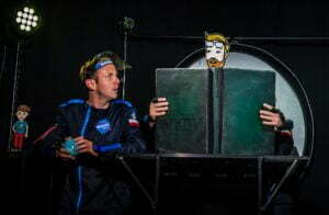 Zdjęcie ze spektaklu Ile waży jabłko na Marsie? Astronauta w granatowym kombinezonie spogląda w prawą stronę zdjęcia na wielką otwartą księgę. Widać ręce osoby, która trzyma księgę, a zza księgi na górze wystaje wycięta z papieru głowa młodego mężczyzny.
