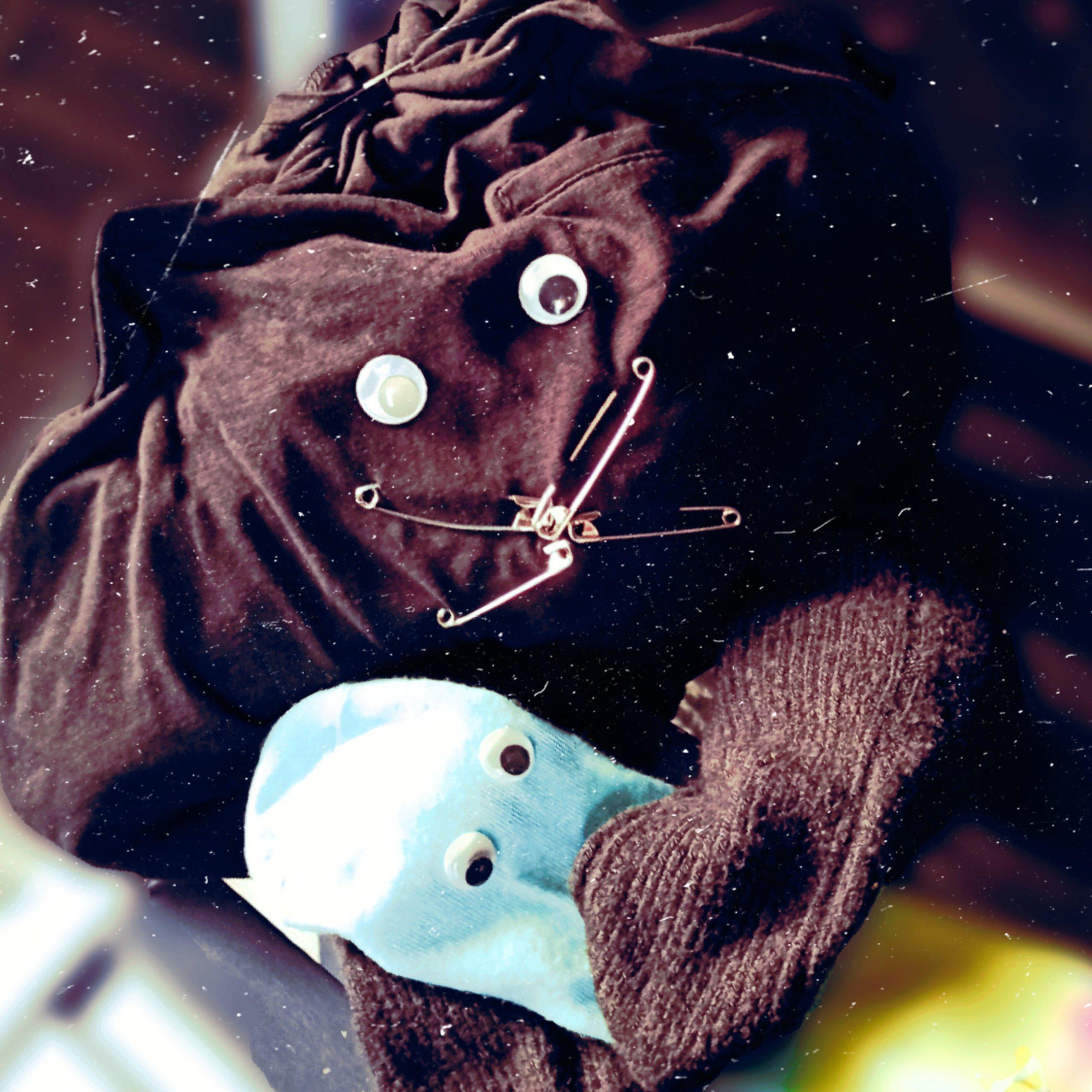 Zdjęcie dwóch skarpetek z nagrania. Niebieskiej z oczami i brązowej z oczami oraz z wąsami z agrafek